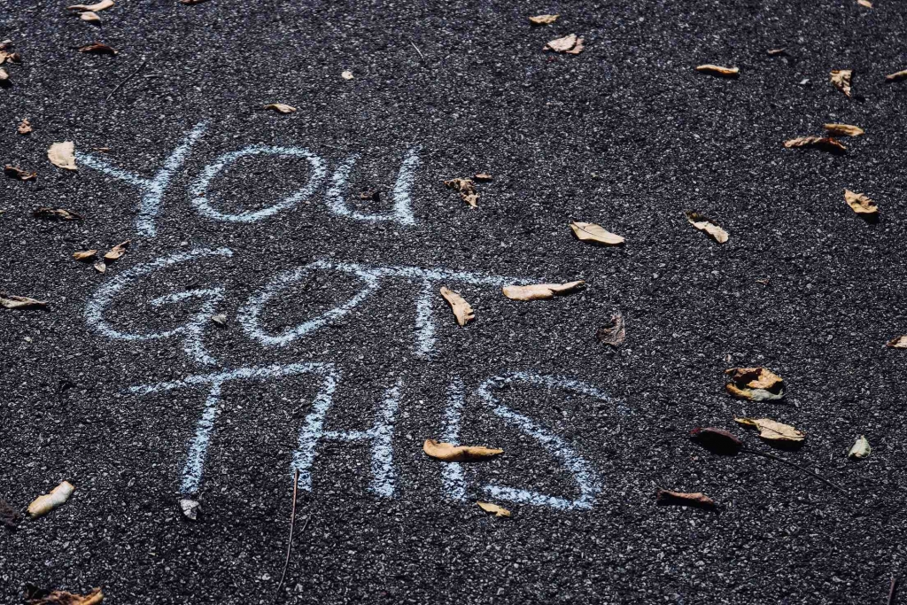 Image of a handful of dry scattered leaves on asphalt with the words YOU GOT THIS written in chalk.